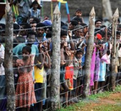 Displaced Sri Lankans stand behind a camp fence. © Sentinel Project