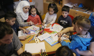 Refugee mothers and children look through games and books in another initiative by the German education ministry, the reading start for refugee children. Photograph: Sean Gallup/Getty Images