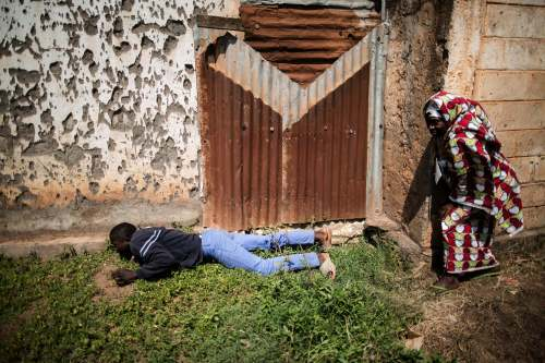 Muslim civilians in Bangui take cover to avoid heavy gunfire directed towards the Baya Dombia school where voters were gathering for the Constitutional Referendum on December 13, 2015. (Photo: Marco Longari / AFP)
