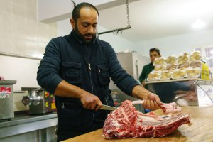 Abu Mohammed, the owner of Sultan Kesap restaurant in the Southern Turkish city of Reyhanli, debones a lamb for meat. His butcher shop/eatery provides his displaced countrymen with culinary reminders of home during better days. Nish Nalbandian